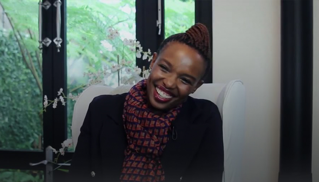 Ayanda Mbanga smiling happily in her office