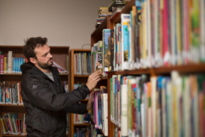 Jonny Wilkinson from The Bookery pulling a book from a bookshelf