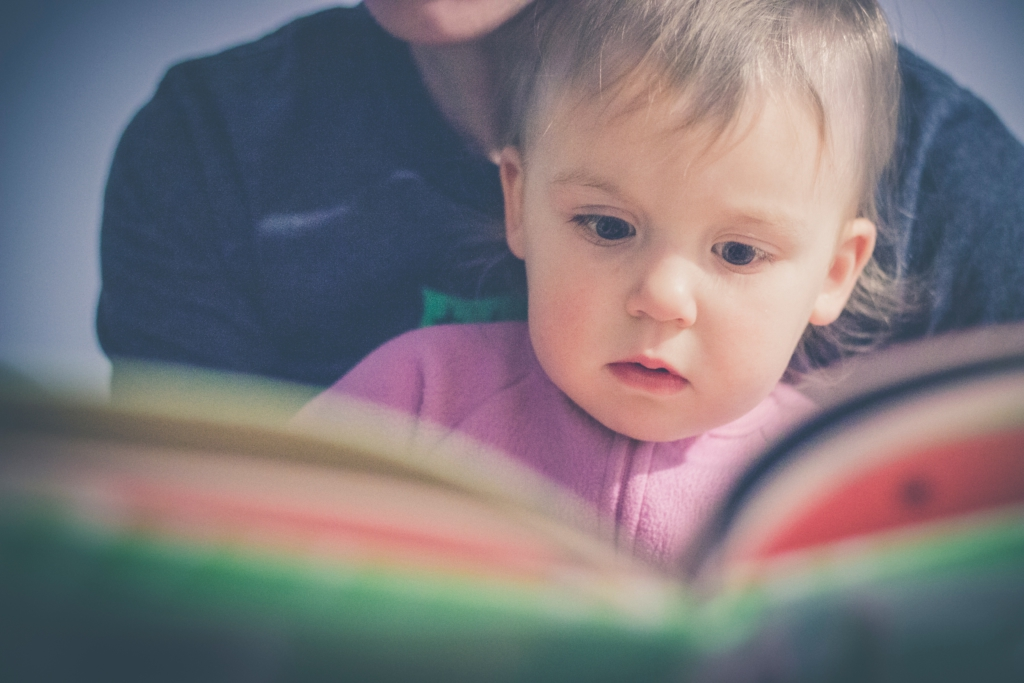 A child on an adult's lap being read to from a book.