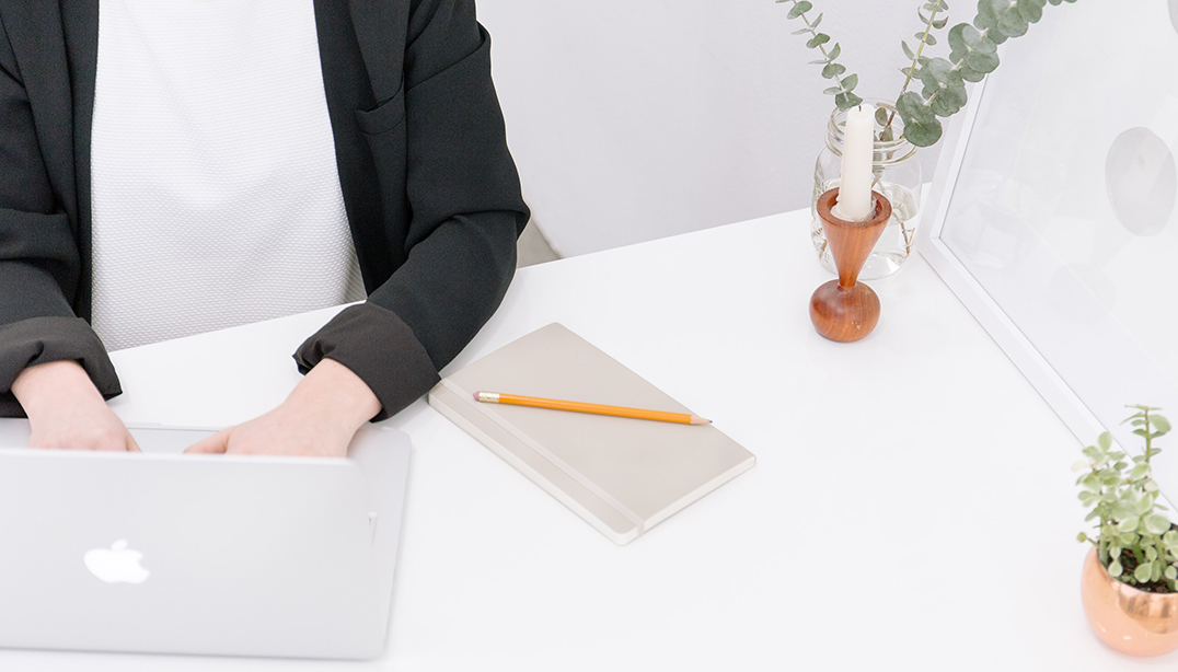 Woman sitting at white desk with laptop, notebook and pencil, two plants and a candle