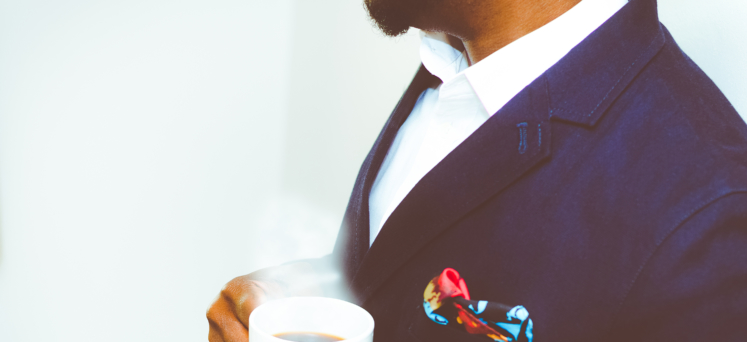 Chest of a man in a suit holding a cup of coffee