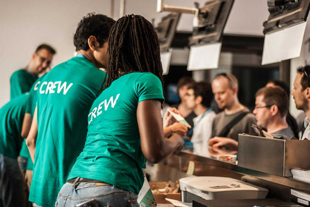 People in green t-shirts with the word 'crew' on the back serving people at a counter