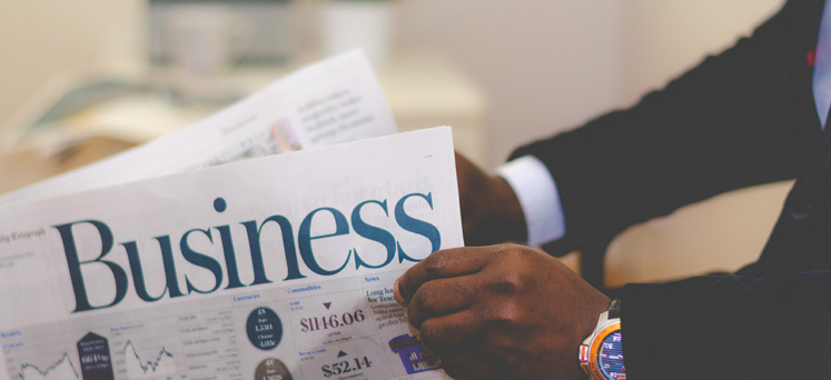 Business newspaper being read by man in suit