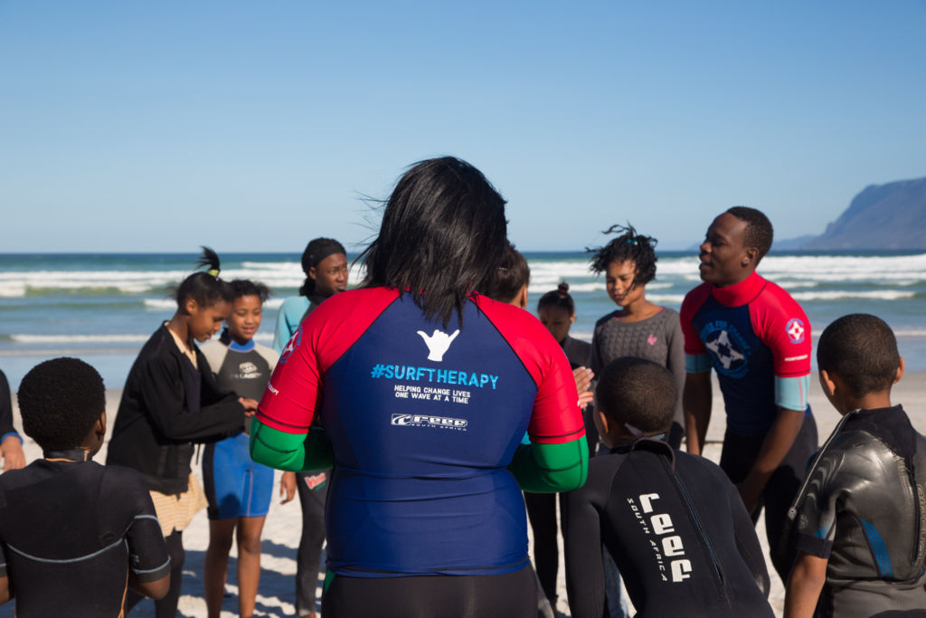 Waves For Change employees and participants in a circle on the beach