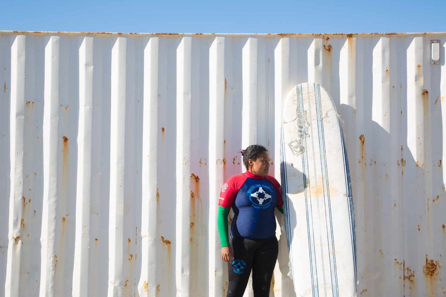 Melreen Devilliers from Waves For Change standing next to a surfboard