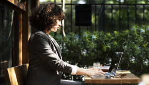 Woman with curly hair sitting outside at a table working on her laptop