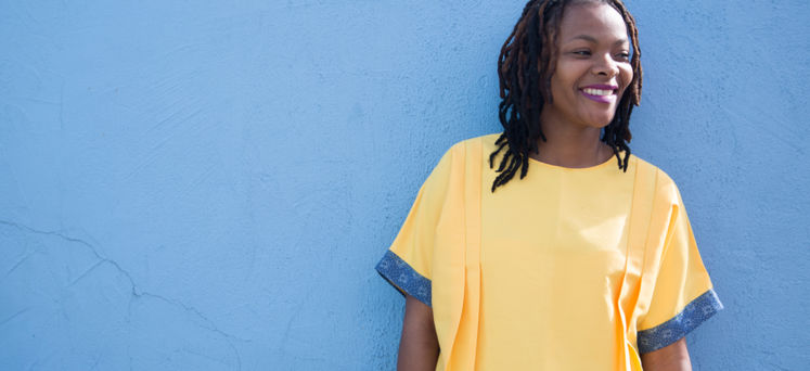 Ayanda Dube in a yellow garment standing against a blue wall