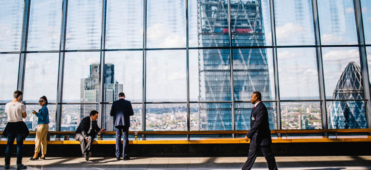 People in a high-rise building with view over London