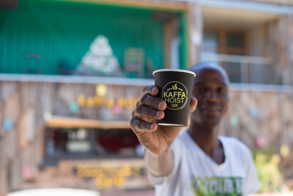 A cup of coffee from Kaffa Hoist Cafe begin held up