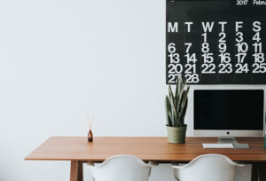 Wooden desk with an iMac and a potted plant with a calendar against the wall