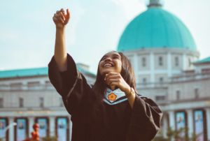 Woman throwing her graduation cap in the air after graduating university